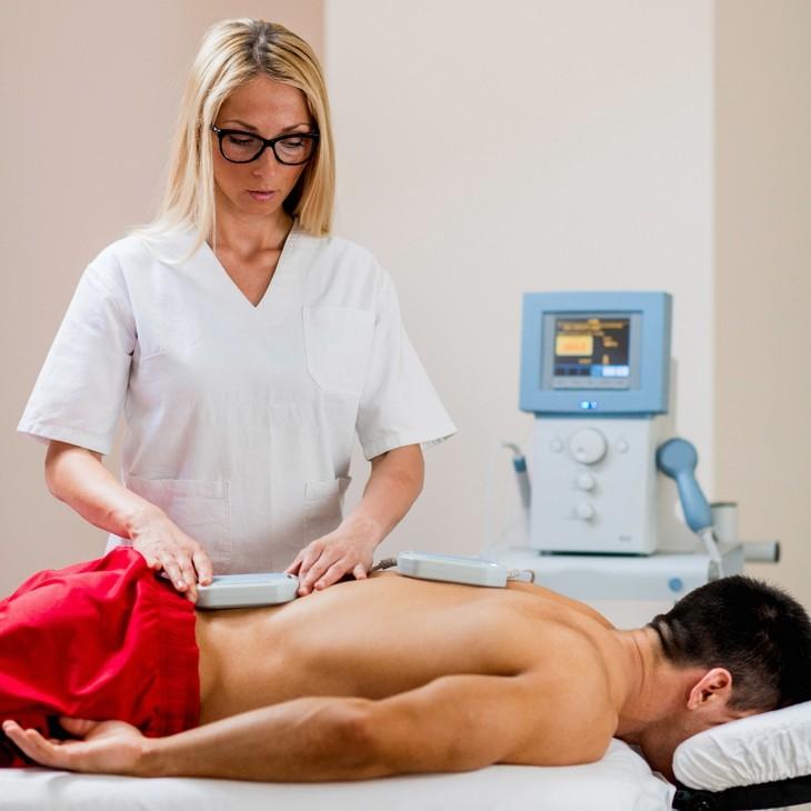 משככי כאבים - סכנות וחלופות: רופאה מטפלת בגבר עם מכשירים חשמליים