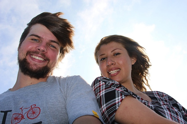 אבני דרך לצמיחה: גבר ואישה ששונים במראה ובצבע העור שלהם מחייכים למצלמה