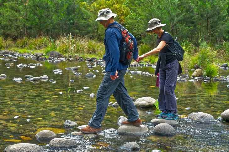 אבני דרך לצמיחה: זוג מחזיק זה בידו של זה והולך דרך אבנים בנהר