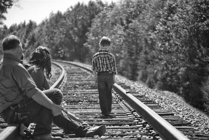 איך לשפר את היחסים עם הילדים החורגים: הורים יושבים על פסי רכבת וילד הולך עליהם