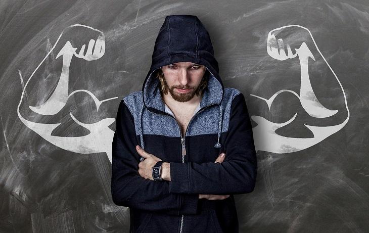 אבני דרך לצמיחה: אדם עומד עם פניו מושפלות וידיו שלובות, שמאחוריו איור על הקיר של זוג ידיים שריריות