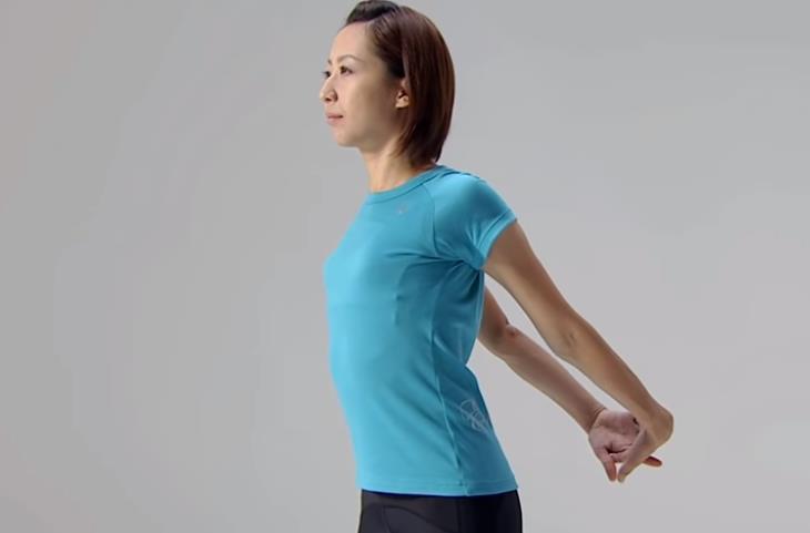 תרגילי גמישות: בחורה משחררת את הכתפיים בעמידה