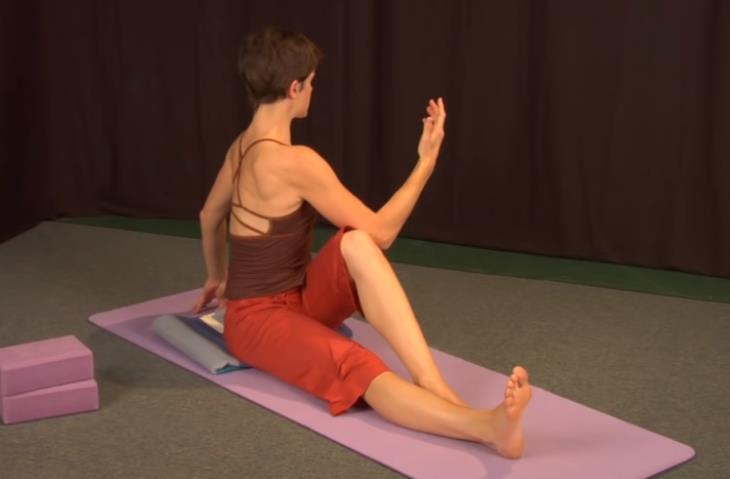תרגילי גמישות: בחורה מבוצעת סיבוב עמוד שדרה בישיבה