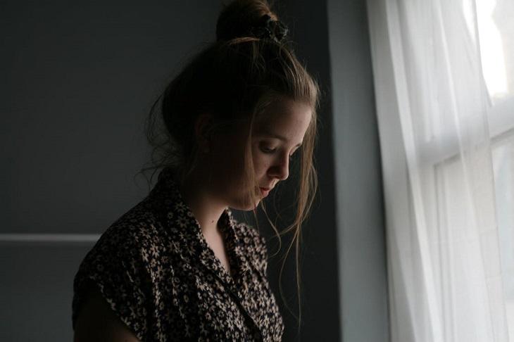 סימנים שמעידים על חוסר סיפוק מהקשר: בחורה עצובה עומדת ליד החלון