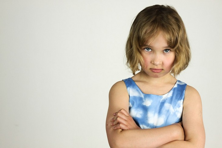 סימנים לילדים עקשנים: ילדה משלבת ידיים ומזעיפה פנים