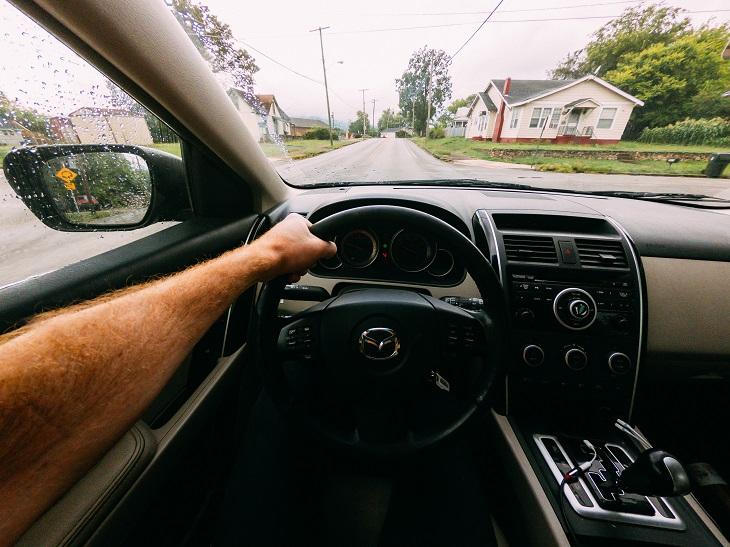 עובדות משעשעות על ביטוח רכב: יד של אדם אוחזת בהגה בזמן נסיעה