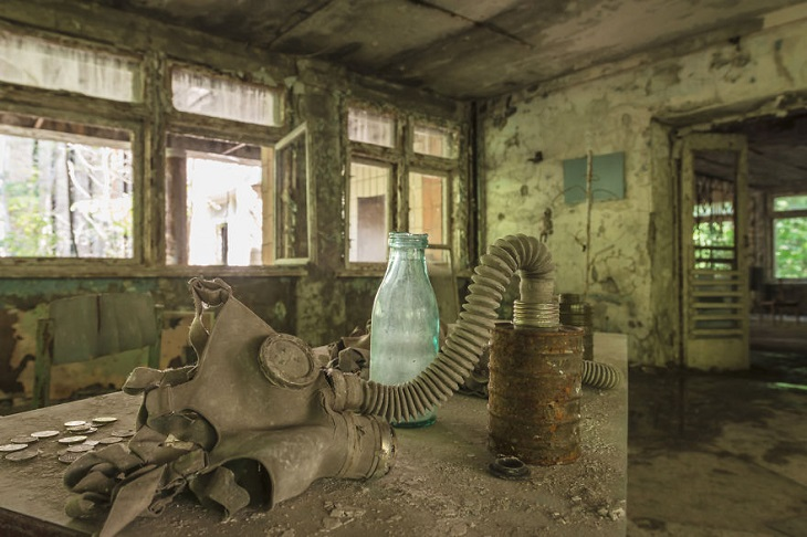 """תיעוד השלכות אסון צ'רנוביל: מסכת אב""""כ, מטבעות ובקבוק על שולחן בחדר הרוס"""