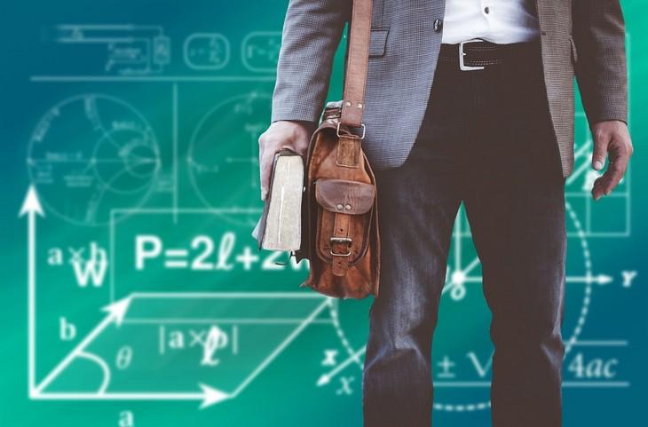 ליל המדענים והמדעניות: פרופסור מחזיק ספר ומאחוריו לוח עם רישומים