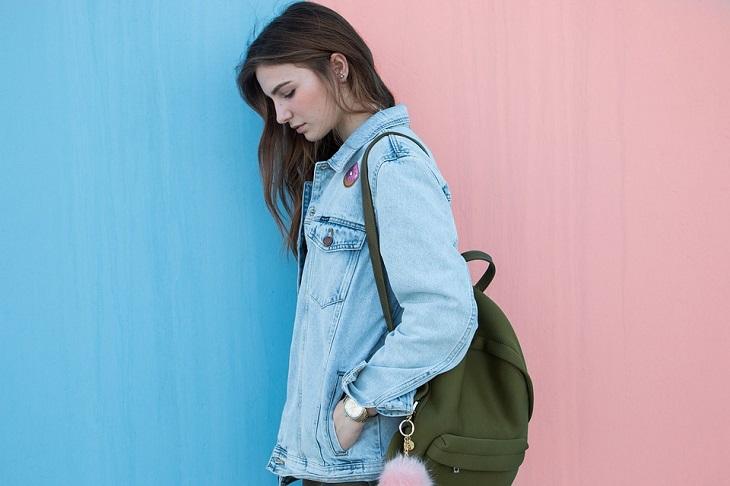 ילקוט כבד: בחורה עצובה עם תיק גב שמונח על כתף אחת