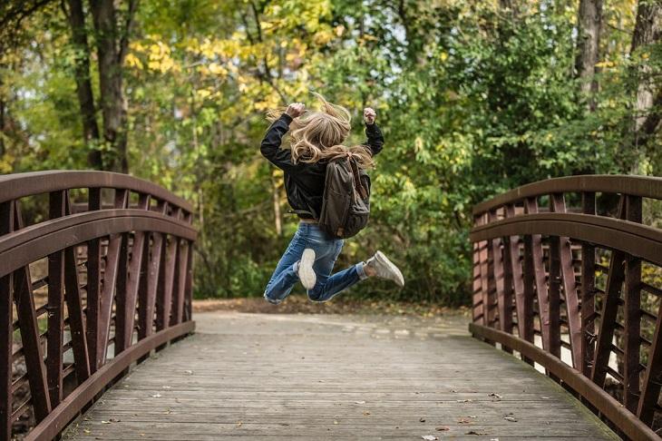 ילקוט כבד: ילדה קופצת עם ילקוט על הגב