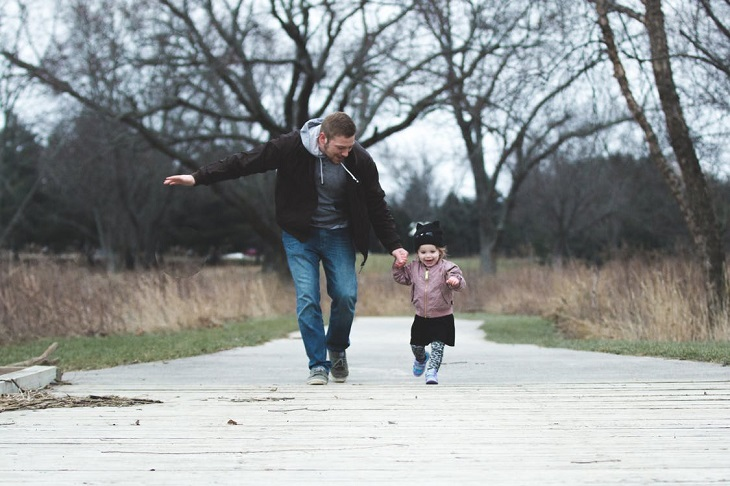 מחוות קטנות של הורים לילדים: אבא ובת רצים על מסלול הליכה בפארק