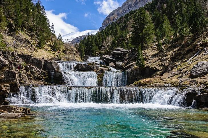טיול לנשים: מפל מדורג בשמורת טבע ירוקה עם הרים ברקע
