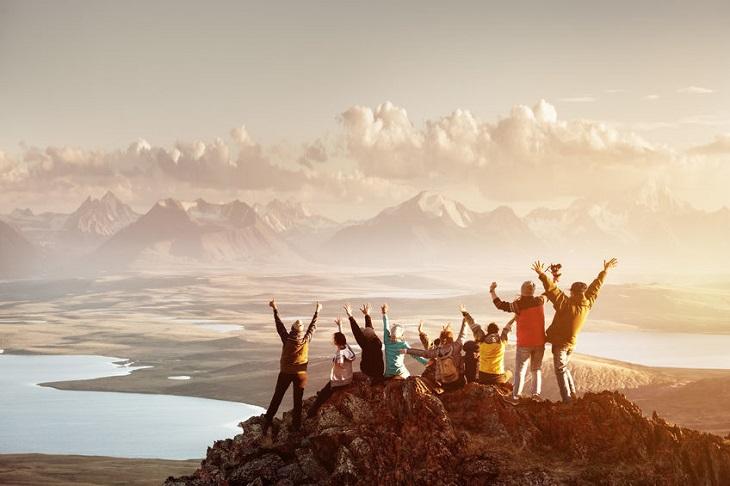 טיול לנשים: נשים על פסגת הר, מרימות ידיים ומסתכלות על הנוף