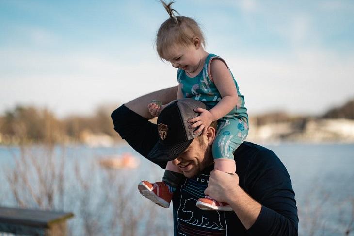 מחוות קטנות של הורים לילדים: אב נושא את בתו על כתפיו והם מחייכים