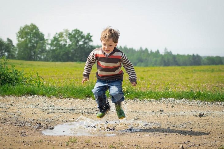 מחוות קטנות של הורים לילדים: ילד קופץ לתוך שלולית ליד דשא
