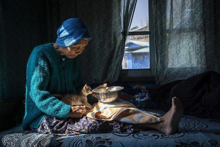 נשים מרחבי העולם: אישה מבוגרת ממיאנמר יושבת על מיטה עם חתול ומביאה לו אוכל