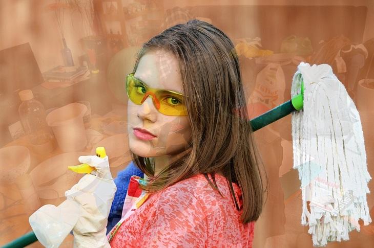 טעויות בניקיון הבית: אישה עם סחבה וחומרי ניקיון על רקע בית מבולגן