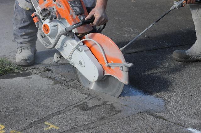 ניסור בטון: איש חותך בטון עם מסור