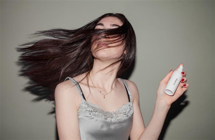 מרכיב מזיק לשיער בשמפו: אישה מנפנפת בשיערה ומחזיקה תכשיר לשיער בידה