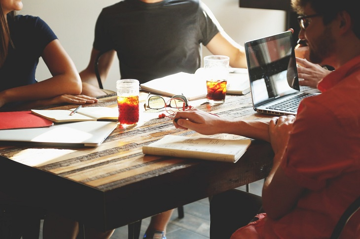 התמודדות עם שתלטנים: אנשים יושבים מסביב לשולחן במקום עבודה