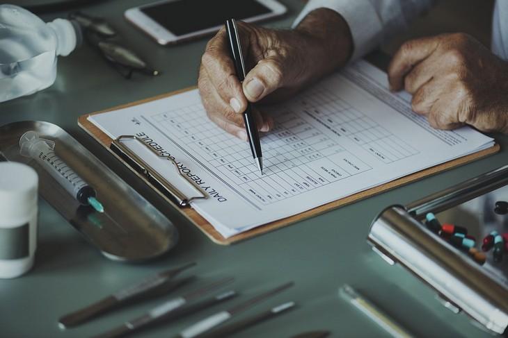 מדריך להתמודדות עם רשלנות רפואית: יד של רופא מסמנת עם עט על דף