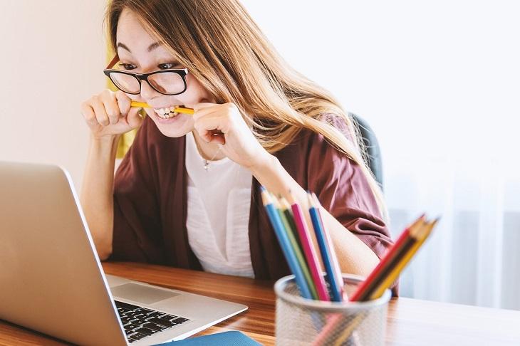 התמודדות עם שתלטנים: אישה יושבת מול המחשב שלה, פותחת עיניים גדולות ותופסת עיפרון בשניה בכעס