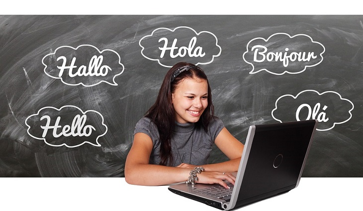 שירות לימוד שפות Memrise: אישה יושבת מול המחשב ומילים בשפות שונות כתובות סביבה