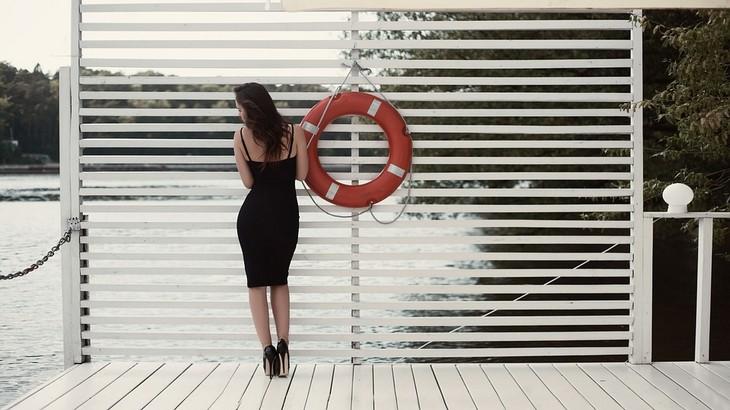 בחירת אישה וגילוי אישיות: אישה עומדת עם הגב למצלמה על רציף