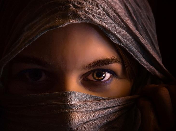 טיפים לשיפור יחסים בין אישיים: ראשה של אישה מכוסה בבד ורק עיניה המסתוריות חשופות