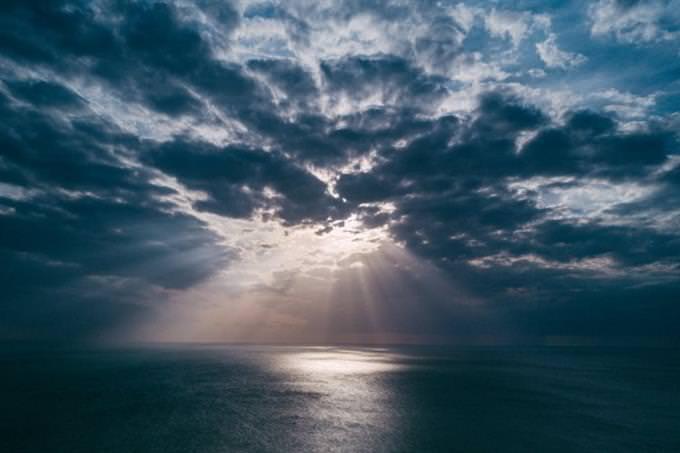 מבחן אישיות של ציירים: שמיים מעוננים מעל ים, שביניהם מבצבצות קרני שמש