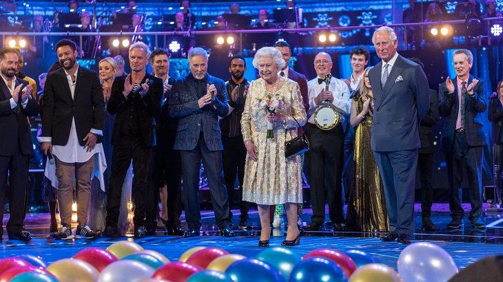 עובדות על משפחת המלוכה הבריטית: המלכה אליזבת עומדת על במה יחד עם בנה הנסיך צ'ארלס ומוזיקאים