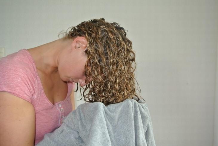 טיפים שכל אישה צריכה להכיר: אישה מייבשת שיער עם חולצת טריקו