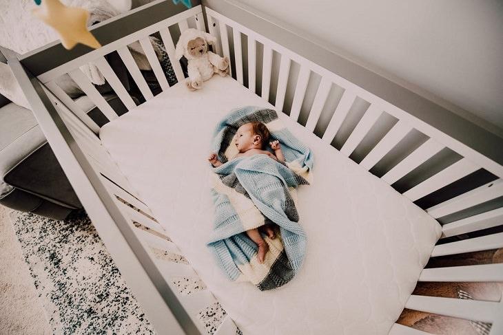 דברים שהורים עושים ומזיקים לילדים: תינוק בעריסה שבפינתה יש בובה