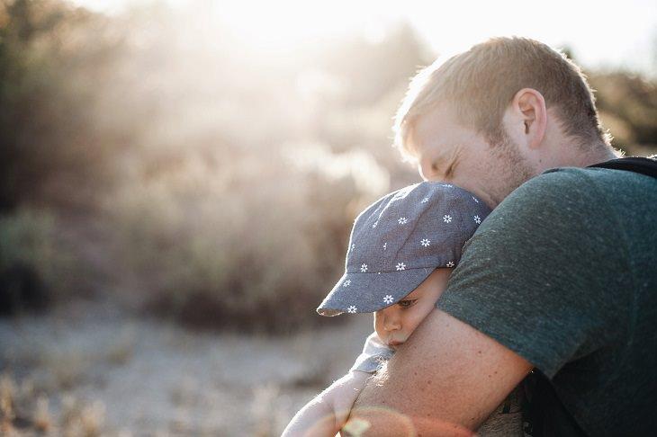 דברים שהורים עושים ומזיקים לילדים: אבא מחבק תינוק בחיק הטבע