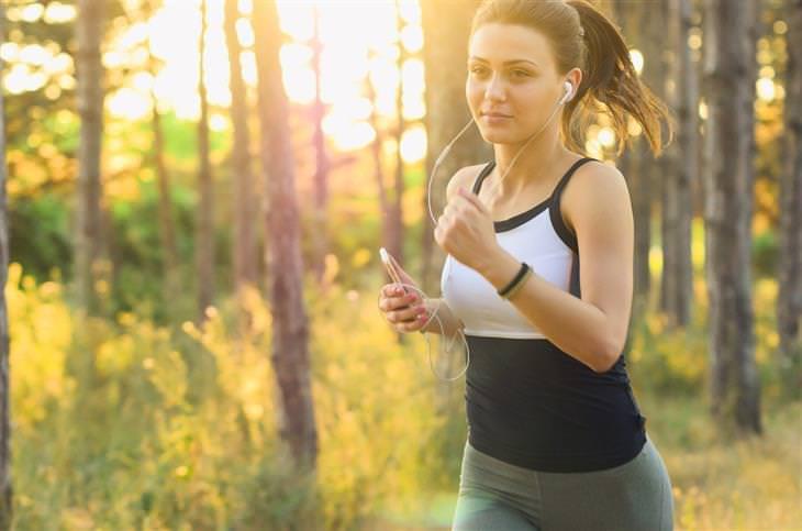 הקשר שבין פעילות גופנית וסרטן: אישה רצה בטבע עם סמארטפון ביד ואוזניות