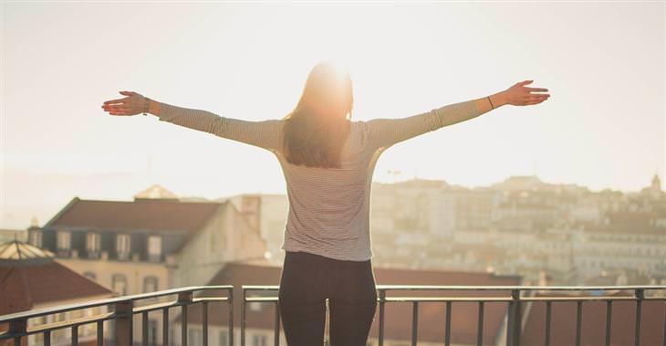 מחקרים על אושר: אישה עומדת על מרפסת ופורשת את ידיה לצדדים