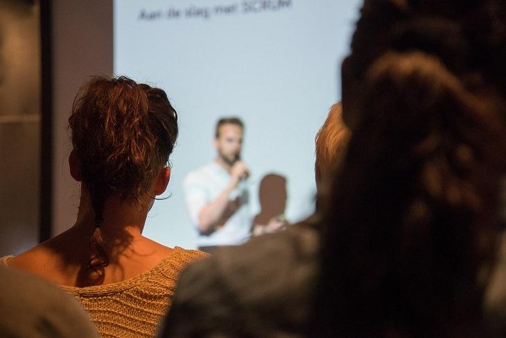 בדיחה על קשישה בהרצאת העצמה: אדם עומד בהרצאה מול קהל
