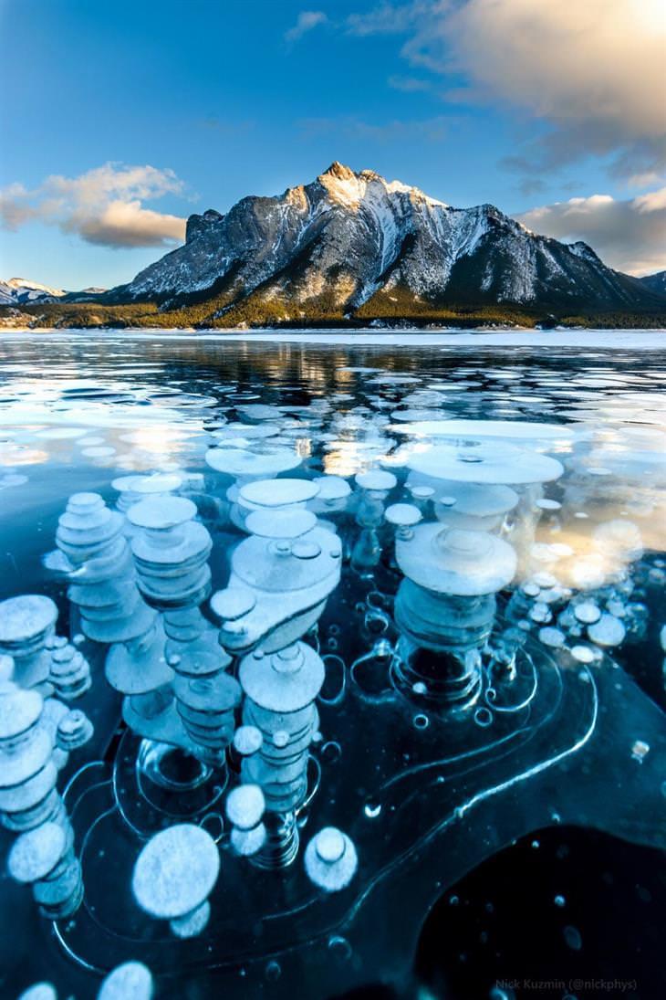 תמונות של נופי טבע: בועות מתאן קפואות באגם מול הר