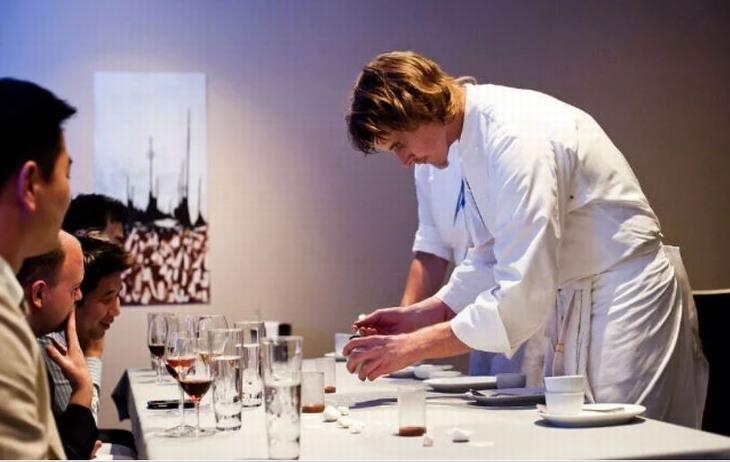 המסעדות הכי אקסקלוסיביות בעולם: שף מכין מנה על צלחת מול סועדים