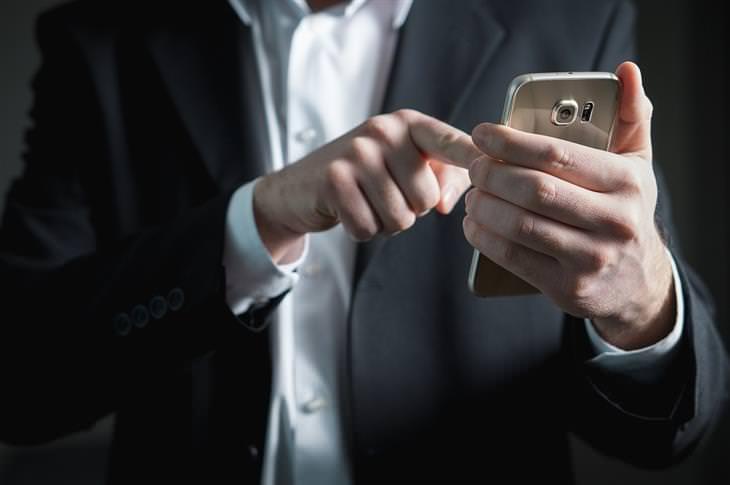 טיפים לאפליקציית וואטסאפ: גבר בחליפה משתמש במכשיר סלולרי