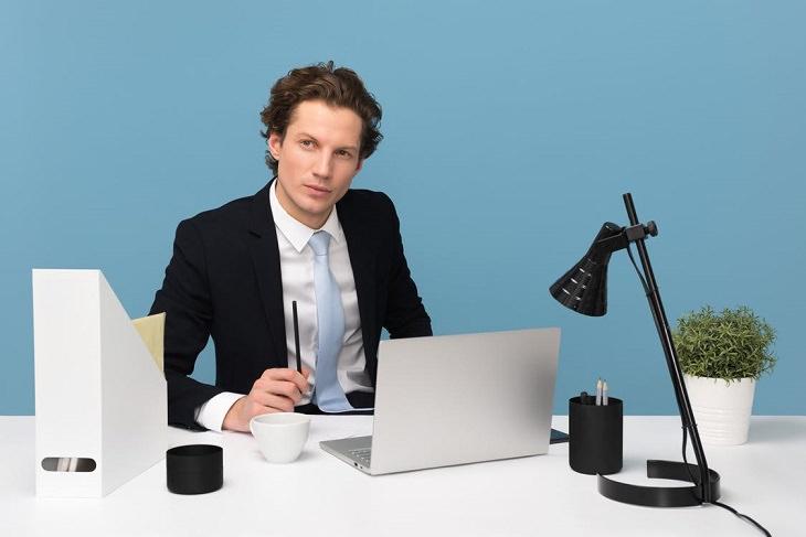 תכונות של אנשים שנועדו לגדולות: בחור יושב עם חליפה לצד שולחן שעליו מחשב נייד ומנורה