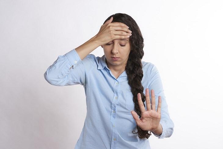 """חשיבת יתר: אישה מחזיקה במצחה ומסמנת בידה """"עצור"""""""