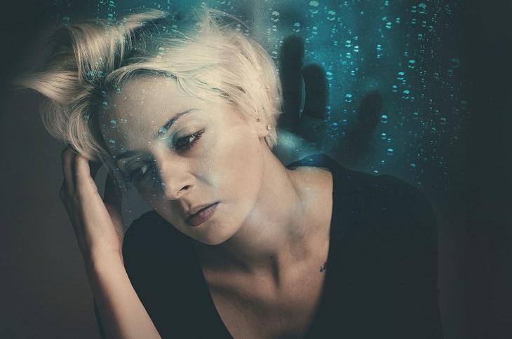 חשיבת יתר: אישה מחזיקה בראשה ונראית מוטרדת, על רקע בועות מים וצללית של יד שבאה לתפוס אותה