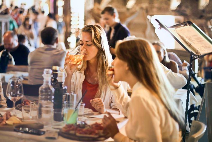 סיבות למה כדאי להביע דעה: בחורה שותה יין ובחורה שנייה אוכלת במסעדה