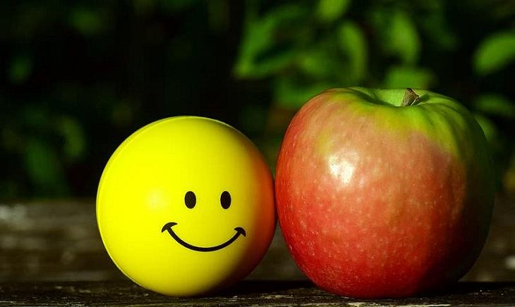 תזונה לאושר ובריאות לפי המדע והיהדות: תפוח עץ ליד כדור שמצוייר עליו פרצוף מחייך