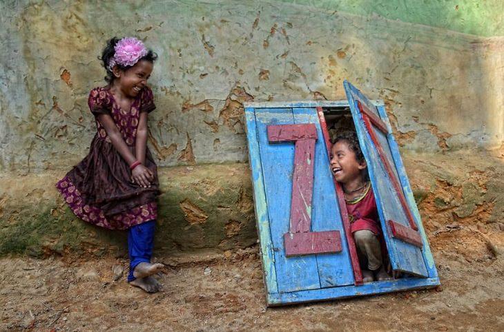 תמונות מתחרות הצילום של סיינה 2020: ילדה משחקת עם ילד שמציץ מחלון מאולתר מעץ