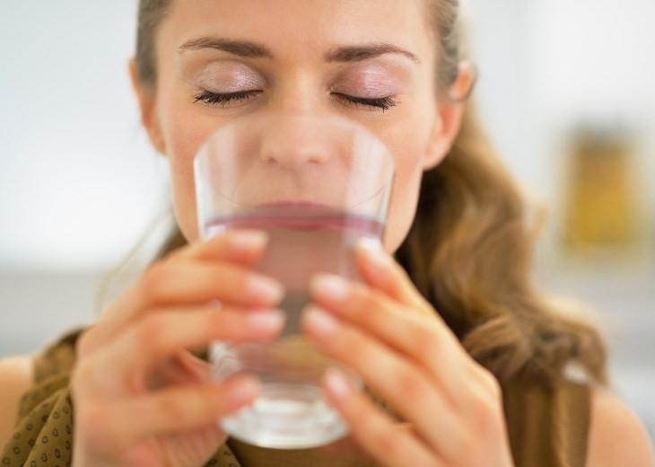 עצות לשמירת בריאות שלפוחית השתן: אישה שותה מכוס מים