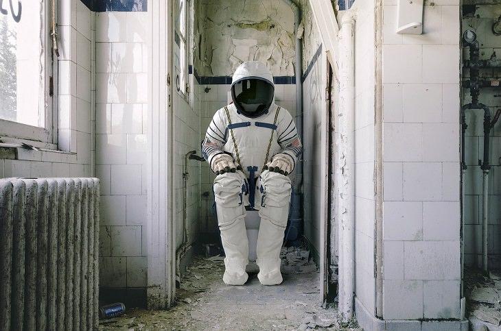 עובדות מעניינות על חקר החלל: אדם בחליפת אסטרונאוט יושב בבית שימוש מפורק