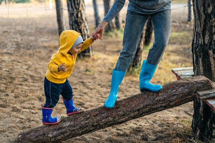 תקשורת אפקטיבית עם ילדים: פעוט הולך עם קורת עץ עם אימו
