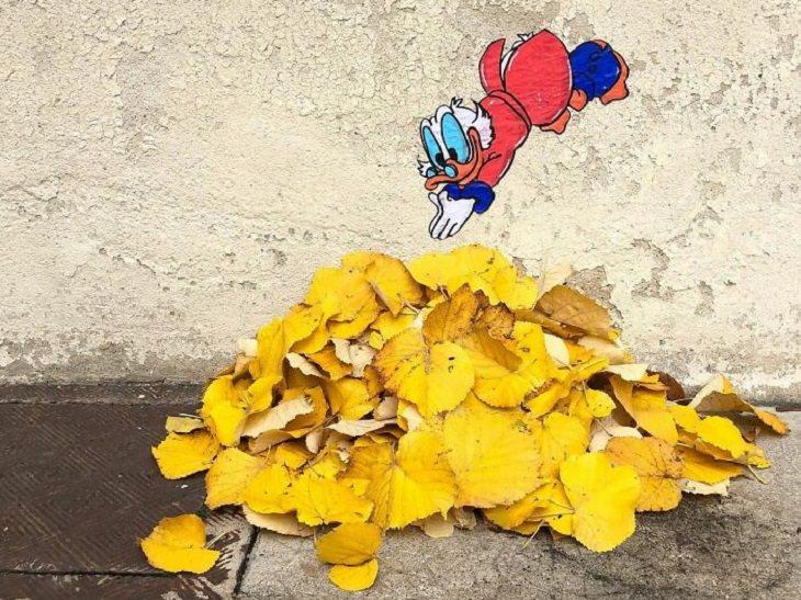 """ציורי רחוב של אמן צרפתי: הדוד קמצוץ מהסדרה """"אגדות ברווזים"""", קופץ לערימת עלים"""